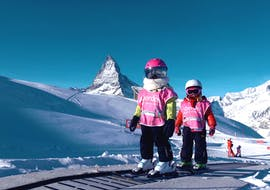Two little girls are riding the magic carpet in the Snowli Kids Village Riffelberg during their Kids Ski Lessons (3-6 years) - Beginners with Zermatters.