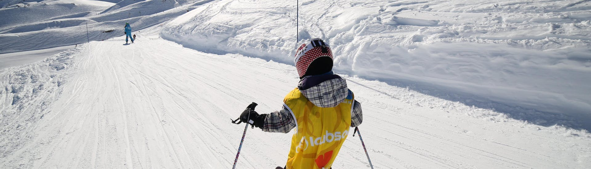 A youg skier is skiing down a snowy slope during his Kids Ski Lessons (3-6 years) - Holiday - All Levels with the ski school ESI Font Romeu.