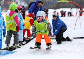 A young child is learning how to ski in the safety of the kindergarten of the ski school Font Romeu during their Kids Ski Lessons (3-6 years) - Low Season - All Levels.