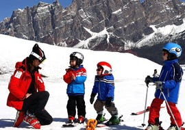 Two young children are learning to ski with their caring instructor from the ski school Scuola Sci Cortina during Kids Ski Lessons (4-10 years) - First Timer.