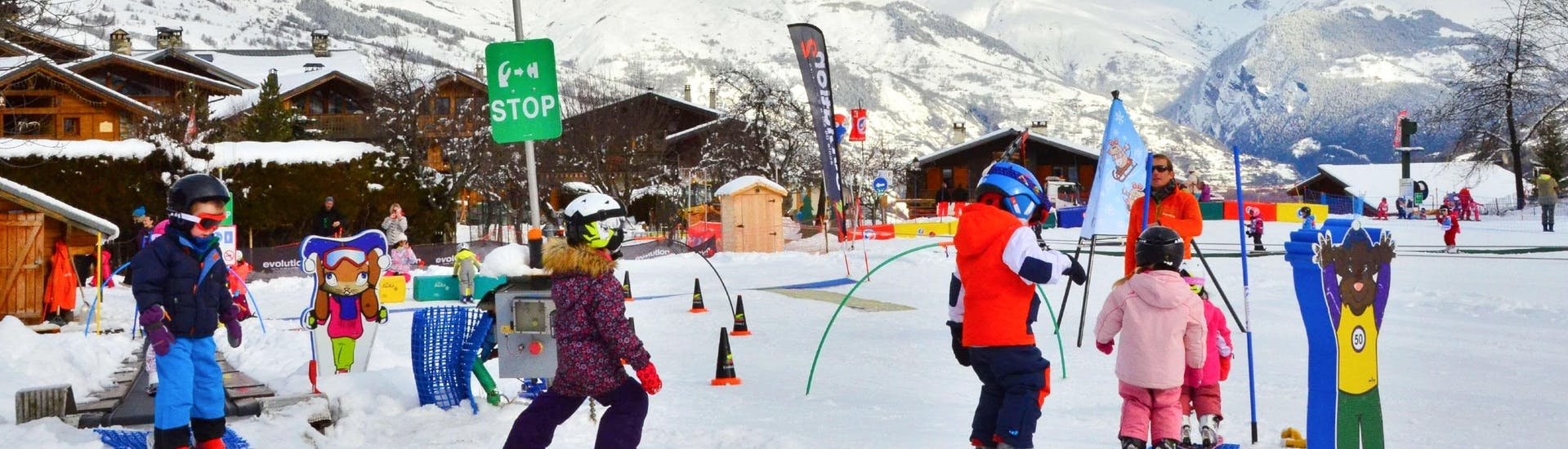 Kids are learning to ski with some games during their Kids Ski Lessons (4-12 y.) for Beginners with the ski school Evolution 2 La Plagne Montchavin - Les Coches.