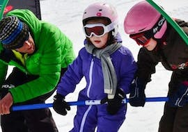 A kid is learning how to ski with the help of his ski instructor from the ski school Evolution 2 La Plagne Montchavin - Les Coches during his Kids Ski Lessons (4-12 y.) for Beginners.