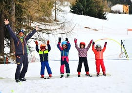 Kids are standing next to each other ready to learn how to ski during their Kids Ski Lessons (4-12 y.) for Beginners - Holidays with the ski school Evolution 2 La Plagne Montchavin - Les Coches.