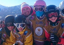 Les enfants posent pour une photo avec leur moniteur de ski de l'école de ski ESF La Foux d'Allos à la fin de leur Cours de ski Enfants (4-12 ans) - Février.