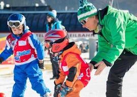 Ein kleiner Junge macht im Rahmen des Kurses Kinder Skikurs (4-12 J.) - Alle Levels - Halbtags unter der Aufsicht einer Skilehrerin der Skischule Snow & Bike Factory Willinge die ersten Schritte auf den Skiern.