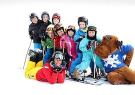 A ski instructor and some young skiers are smiling at the camera during the Kids Ski Lessons (4-12 y.) - All Levels - Holidays organized by the ski school Scuola di Sci Verena in the ski resort of Asiago.