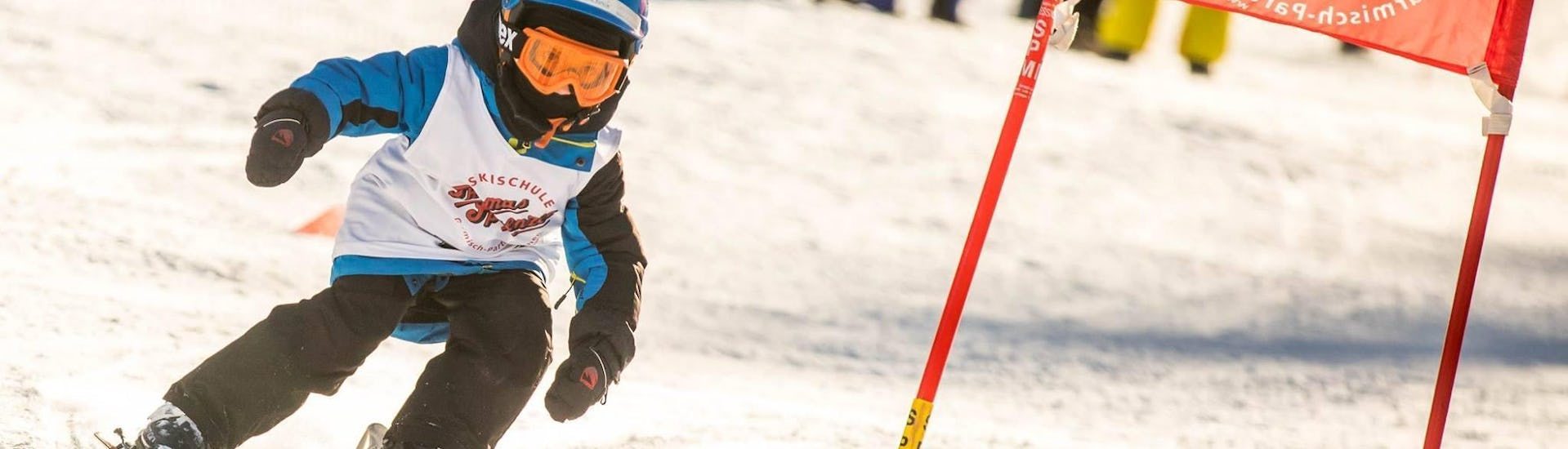 A young child is racing down a race course as part of its Kids Ski Lessons (4-12 years) - All Levels with the ski school Skischule Thomas Sprenzel in the ski resort of Garmisch-Classic.