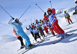 Children and ski instructor have fun during the Kids Ski Lessons (4-12 years) - Christmas of the ski and snowboard school Scuola di Sci e Snowboard Prato Nevoso.