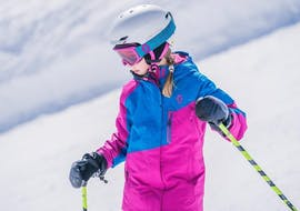 During the Kids Ski Lessons (4-13 years) - All Levels, a young girl is taking the first steps on skis under the supervision of an experienced ski instructor from WIWA | DSV Skischule & Skiverleih.