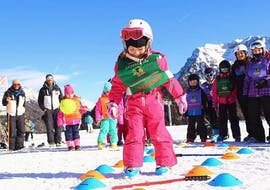 A little kid having fun in front of the Maestri di Sci Moena Ski School after the Kids Ski Lessons (4-14 y.) for All Levels.
