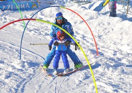 A ski instructor helps a child to ski down the slope during the Kids Ski Lessons (4-14 y.) - Half Day - First Timer of the ski school Scuola di Sci Azzurra Livigno.