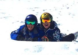Deux enfants sont allongés dans la neige pendant leur Cours de ski Enfants (4-14 ans) - Haute saison - Débutant et s'amusent avec leur moniteur de ski de l'école de ski Scuola di Sci Bardonecchia.