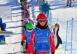 Die Kinder sind auf dem Zauberteppich in einer Reihe aufgestellt, ein ideales Gerät, das die Kleinen aus dem Kinder Skikurs von 4-14 Jahren unterstützt - Feiertage für Kinder ohne Erfahrung der Skischule Scuola di Sci Azzurra Livigno.