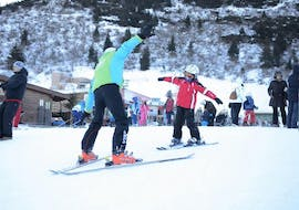 A young skier is trying to master a slope with his ski instructor during the Kids Ski Lessons (4-14 y.) - Christmas - All Levels organized by Maestri di Sci Cristallo - Monte Bondone in the ski resort of Monte Bondone.
