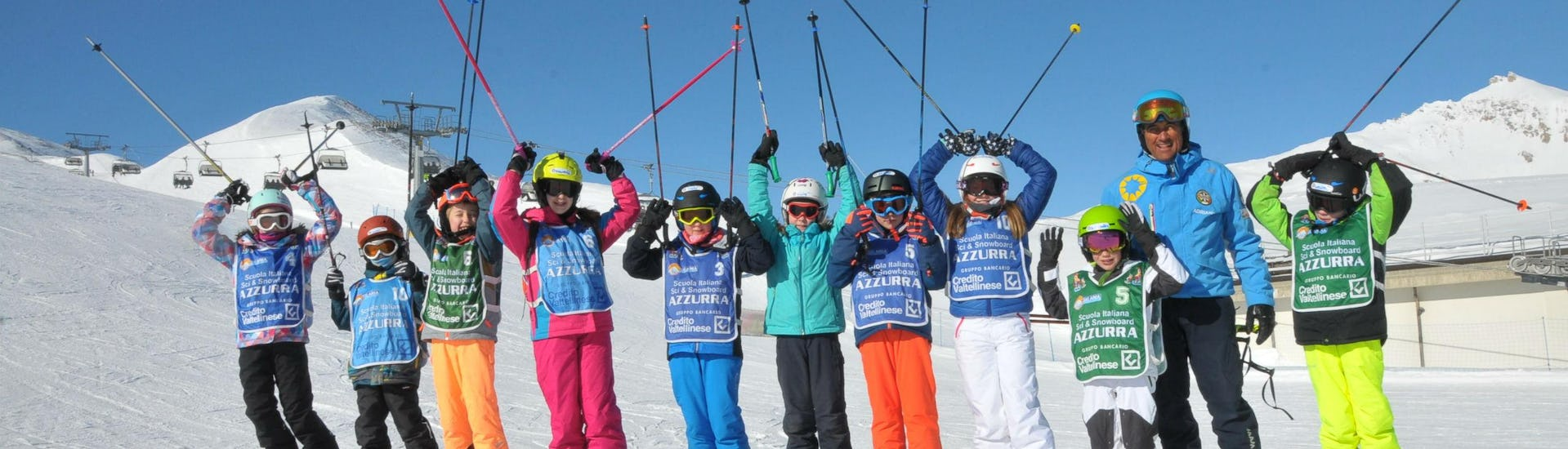 A group of children is enjoying their Kids Ski Lessons (4-14 y.) - Full Day with the ski school Scuola di Sci Azzurra Livigno on the ski slopes of Livigno.