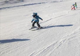 A young skier is mastering a slope during the Kids Ski Lessons (4-14 y.) - With Experience organized by the ski school Scuola di Sci Tre Nevi Ovindoli in the ski resort of Ovindoli on the Monte Magnola.