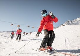 A ski instructor is explaining the basics of skiing to some young skiers during the Kids Ski Lessons (4-15 years) - All Levels organized by the ski school Ski & Snowboardschool Vacancia in the ski resort of Sölden.