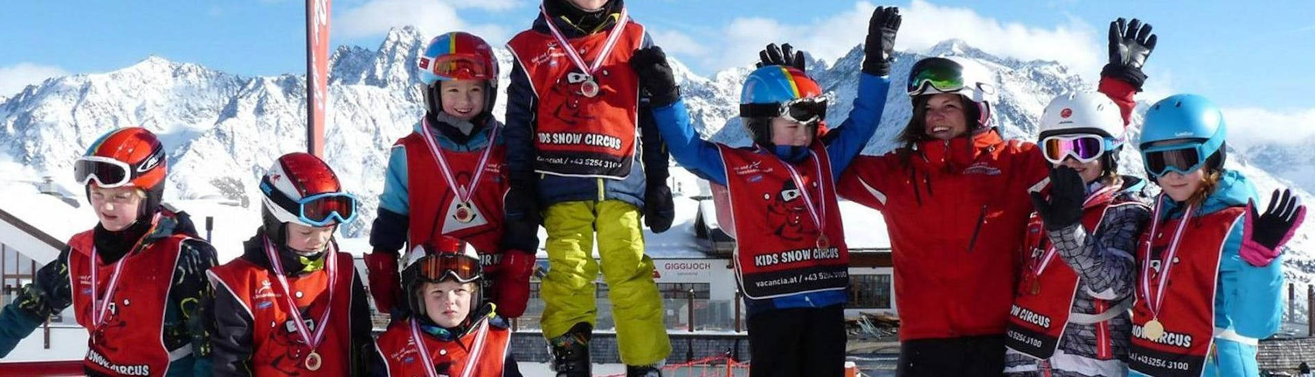 A group of children is enjoying a medal ceremony as part of their Kids Ski Lessons (4-15 years) - All Levels with the ski school Ski- und Snowboardschule Vacancia.
