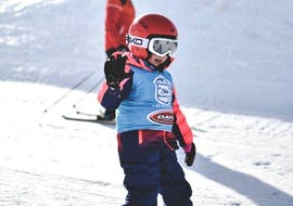A child waves cheerfully during its Kids Ski Lessons (4-17 y.) for all Levels from the Escuela Ski Cerler and learns the basic techniques of skiing.