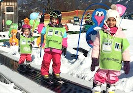 A group of children is enjoying the Kids Ski Lessons (4-6 years) - All Levels in the safe environment of the school Alpin Skischule Oberstdorf.