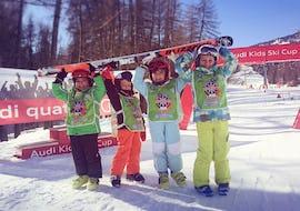 Eine Gruppe lächelnder Kinder nach dem Abschlussrennen ihres Kinder Skikurs (4-6 Jahre) - Anfänger mit der Skischule Scuola di Sci e Snowboard Cristallo Cortina.