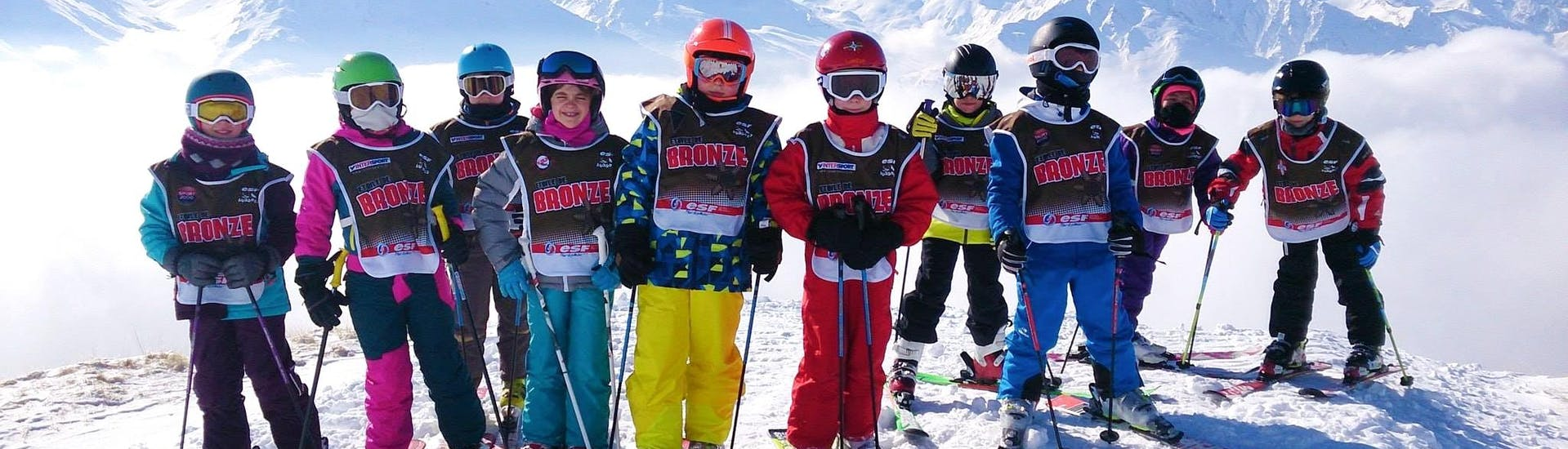 Kids are taking a picture in front of a snowy background at the end of their Kids Ski Lessons (5-12 y.) for All Levels with the ski school ESF Aussois.