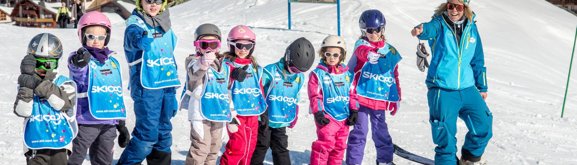 Kids are standing next to each other taking a picture with their ski instructor from the ski school Ski Cool Val Thorens during their Kids Ski Lessons (5-12 y.) - Morning - Holiday - 1st Timer.