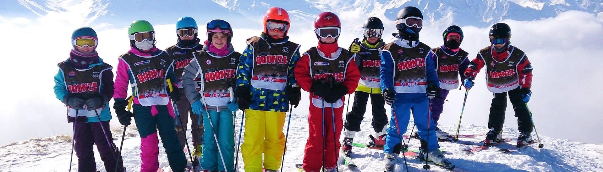 """Kids are taking a picture in front of a snowy background at the end of their Kids Ski Lessons """"Top 8"""" (5-12 y.) - February with the ski school ESF Aussois."""