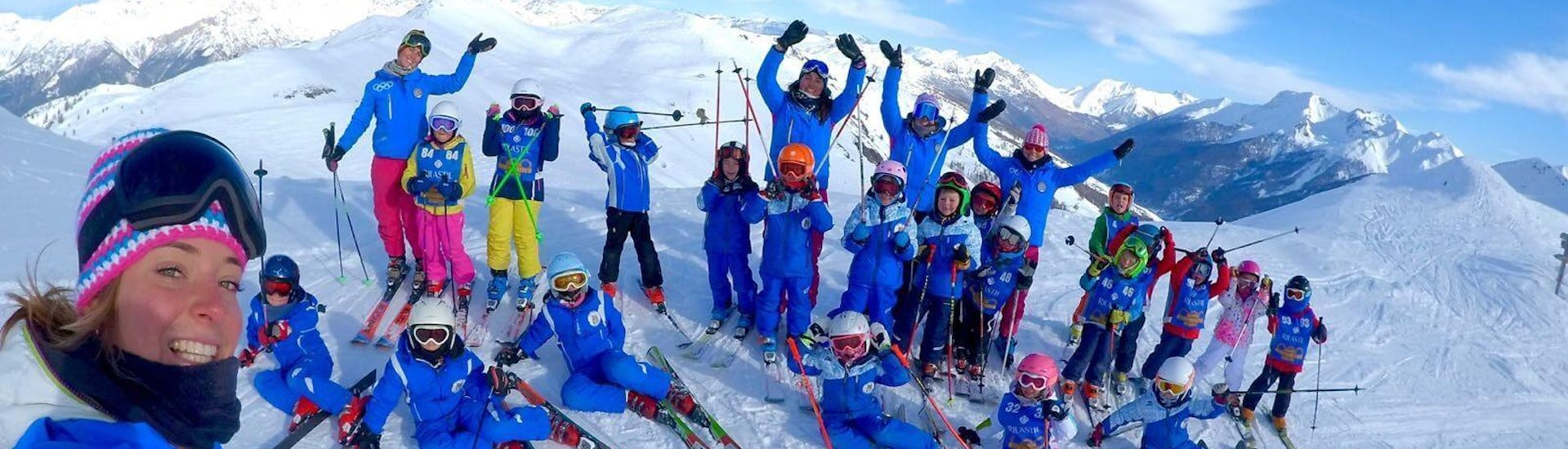 A group of children and their ski instructors from the ski school Scuola di Sci Olimpionica are posing for a photo on top of the mountain in Sestriere, before they get started with their Kids Ski Lessons (5-12 y.) - Advanced.