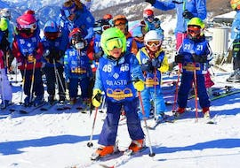 A kid is having fun on the slopes of the Via Lattea ski resort in Sestriere during the Kids Ski Lessons (5-12 y.) - Advanced organized by the ski school Scuola di Sci Olimpionica.