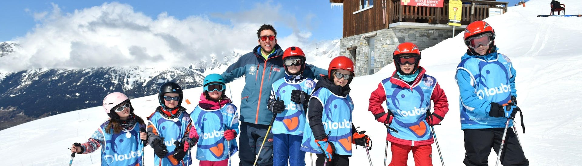 Kids are standing next to each other similing at the top of the mountain during their Kids Ski Lessons (5-12 years) - All Levels with the ski school ESI Valfréjus.