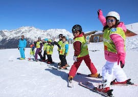 Young skiers are standing in line behind their ski instructor from the ski school ESI Valfréjus waiting to start their Kids Ski Lessons (5-12 years) - All Levels.