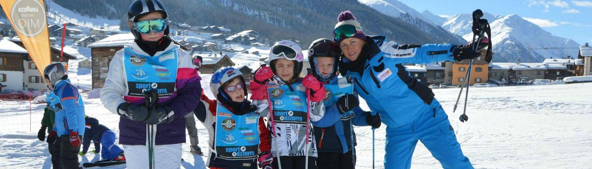 Un gruppo di bambini si diverte con le lezioni di sci per bambini (5-12 anni) - Tutti i livelli insieme al loro maestro della Scuola di Sci e Snowboard Livigno Italia.