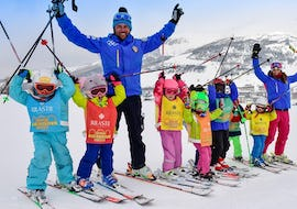A group of young skier is having fun with the ski instructor of the Kids Ski Lessons (5-12 y.) - Beginner organized by the ski school Scuola di Sci Olimpionica in Sestriere.