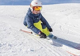 A young skier is skiing down a slope during his Kids Ski Lessons (5-12 years) - Experienced with the ski school Moonshot La Bresse.