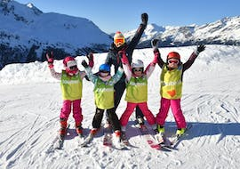 A group of skiers is standing at the top of the slope with their arms in the air with their ski instructor from the ski school ESI Valfréjus during their Kids Ski Lessons (5-12 years) - Holiday - All Levels.
