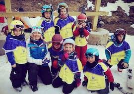Mehrere Kinder posieren nach ihrem Kinder Skikurs (8-12 Jahre) - Nebensaison - Anfänger gemeinsam mit ihrem Skilehrer der Skischule Moonshot La Bresse für ein gemeinsames Gruppenfoto.