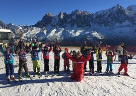 Kids are standing next to each other with their ski poles up in the air during their Kids Ski Lessons (5-12 years) in Chamonix/Savoy with the ski school ESF Chamonix.