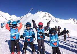 De jeunes skieurs se tiennent devant une montagne enneigée, prêt pour leur Cours de ski pour Enfants (5-13 ans) - Après-midi avec l'école de ski ESI du Tourmalet à La Mongie.
