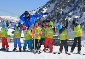 Young skiers are standing next to each other with their ski poles in the air during their Kids Ski Lessons (5-13 ans) - Morning with the ski school ESI du Tourmalet in La Mongie.