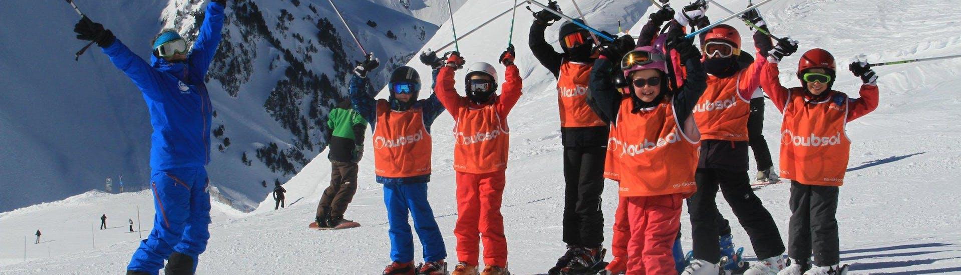 Unos jovenes esquiadores están parados uno al lado del otro con sus bastones de esquí en el aire durante sus Clases de esquí para niños (5-13 años) - Mañana con la escuela de esquí ESI du Tourmalet en La Mongie.