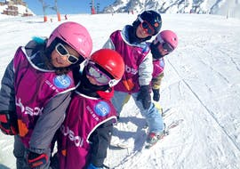 Young skiers are standing in line while skiing during their Kids Ski Lessons (5-13 years) - Weekend with the ski school ESI du Tourmalet in La Mongie.