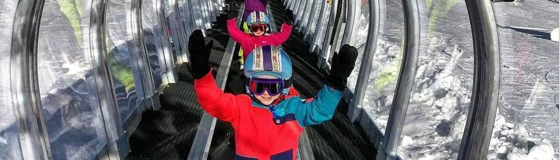 De jeunes skieurs utilisent avec joie le tapis magique de l'école de ski ESI Easy2Ride Morzine pendant leur Cours de ski pour Enfants (5-13 ans) - Après-midi - Débutant.