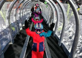 Young skiers are happily riding the magic carpet of the ski school ESI Easy2Ride Morzine during their Kids Ski Lessons (5-13 y.) - Afternoon - Beginner.