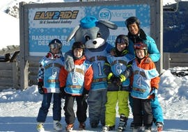 Children are posing in front of the camera around the mascot of the ESI Easy2Ride Morzine ski school during their Kids Ski Lessons (5-13 y.) - Morning - Beginner.