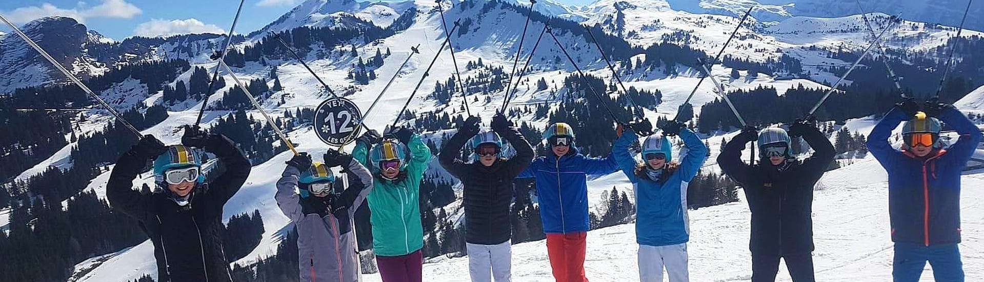 Au sommet des pistes, des skieurs lèvent leurs bâtons de ski vers le ciel pendant leur Cours de ski pour Enfants (5-13 ans) - Après-midi - Avancé avec l'école de ski ESI Easy2Ride Morzine.
