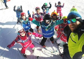 A group of little ski enthusiasts is having fun with their ski instructor from the ski school Prosneige Val d'Isère during the Kids Ski Lessons (5-13 years) - All Levels.
