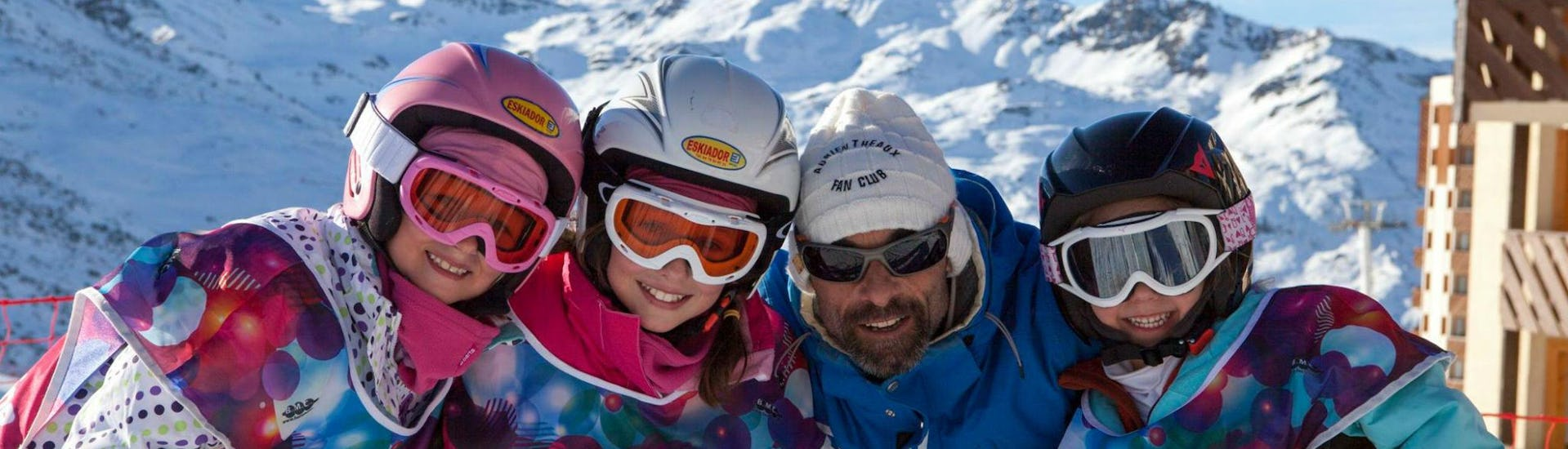 A group of children in full skiing gear are smiling at the camera together with their ski instructor from the ski school Prosneige Val Thorens & Les Menuires while preparing for their Kids Ski Lessons (5-13 years) - All Levels.