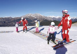 A group of kids is learning to ski during Kids Ski Lessons (5-13 years) - All Levels with the ski school Scuola Nazionale Sci e Snow Monte Pora.