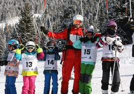 A group of children is posing for a group picture with their ski instructor from the ski school Skischule Lechner in Zell am Ziller during their Kids Ski Lessons (5-14 years) - Advanced.